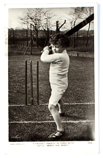 An original postcard photograph of a young boy standing at the wicket, bat raised.